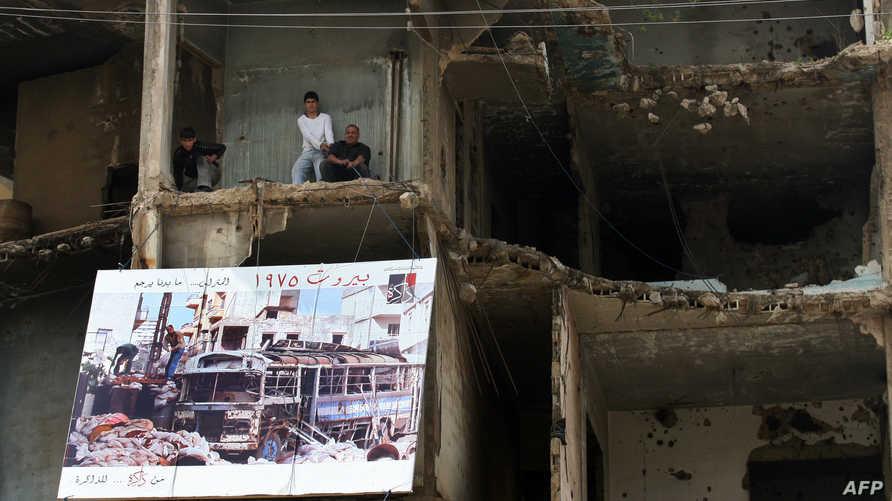 رفع ملصق عن الحرب الأهلية اللبنانية على أحد المباني المدمرة على أحد خطوط تماس هذه الحرب (أرشيف)