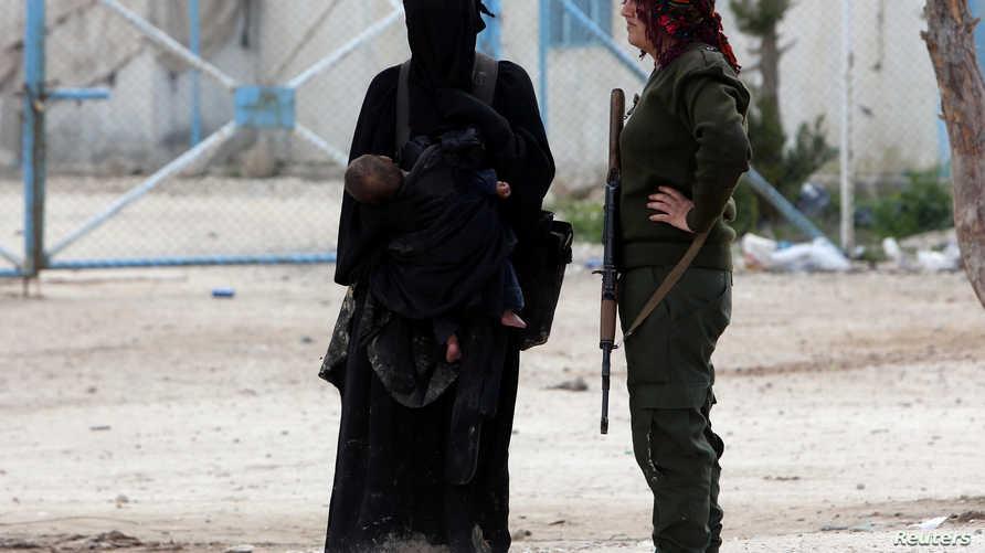 زوجة أحد مقاتلي داعش تقف إلى جانب مقاتلة من قوات سوريا الديمقراطي في مخيم الهول في الحسكة