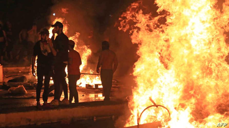 متظاهرون يشعلون النيران لقطع الطريق على قوات الأمن التي تلاحقهم في كربلاء، الجمعة، 25 أكتوبر