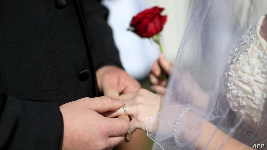 زوجان يتبادلان خاتمي الزواج في عيد الحب
