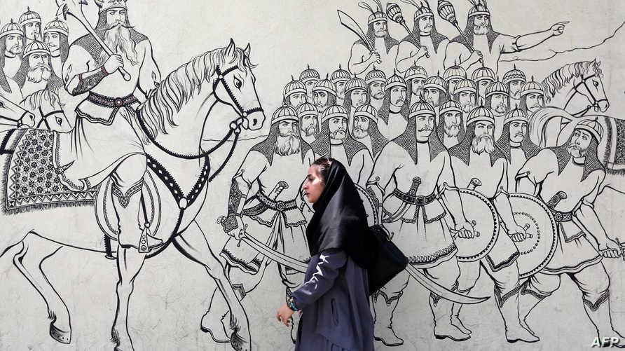 إيرانية تمر أمام غرافيتي يمثل قصيدة فارسية قديمة، في أحد شوارع طهران