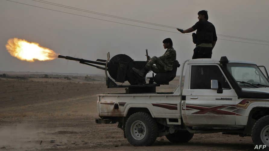 عنصران من المليشيات السورية الموالية لتركيا يطلقان النيران تجاه المناطق الكردية شمال سوريا