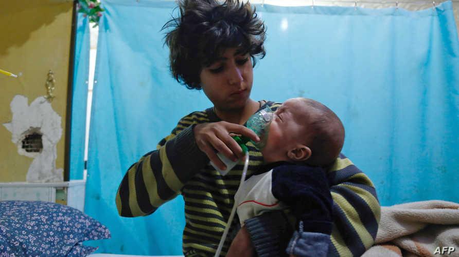 صبي سوري يضع رضيعا على الأكسجين في مدينة دوما