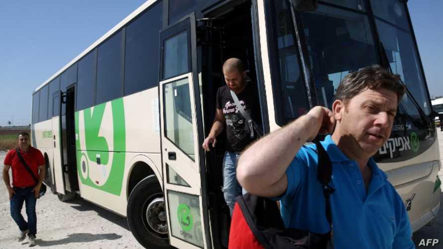 عمال فلسطينيون ينزلون من حافلة إسرائيلية عند معبر إيال قرب بلدة قلقيلية في الضفة الغربية، للعودة إلى منازلهم بعد يوم عمل في إسرائيل.