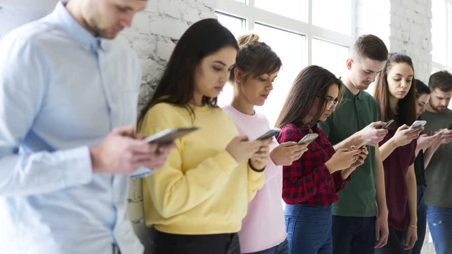 مراهقون يستخدمون هواتفهم الذكية . تعبيرية