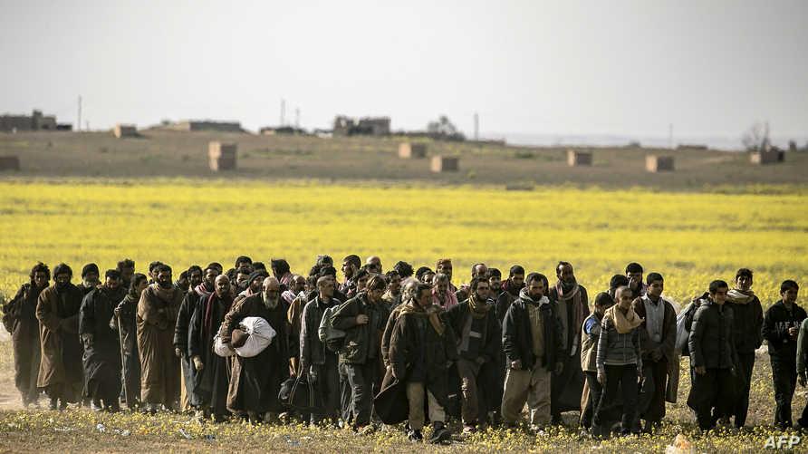 رجال يشتبه في انتمائهم لتنظيم داعش يتوجهون نحو نقطة تفتيش أميركية كردية في الباغو بسوريا-أرشيف