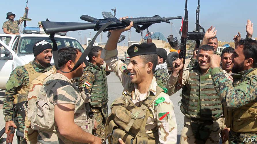 جنود عراقيون يلوحون بأسلحتهم. أرشيف