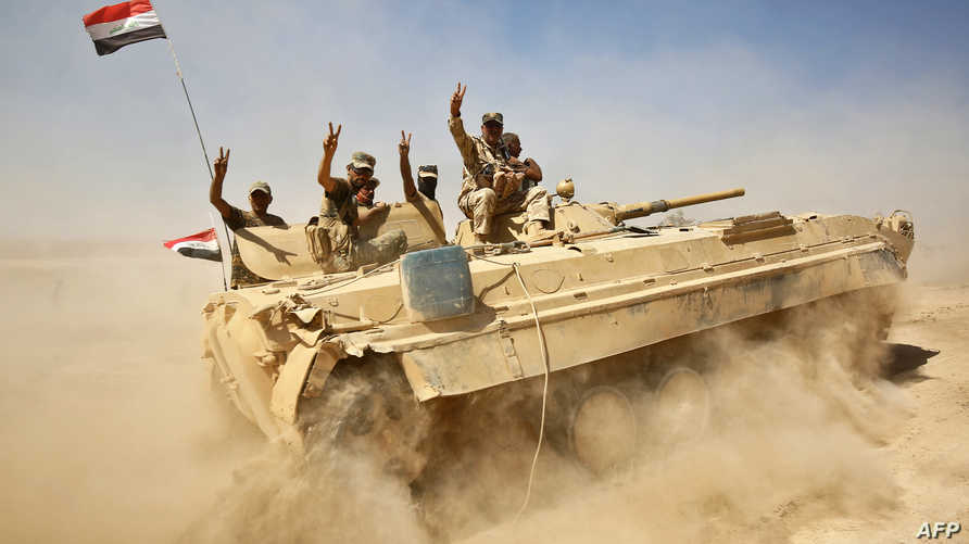 عناصر في القوات العراقية المشتركة يرفعون العلم العراقي بعد تحرير تلعفر