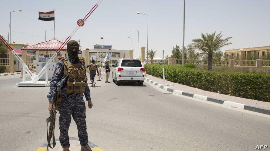 جندي عراقي يحرس مدخل حقل الزبير النفطي بعد استهداف صاروخ كاتيوشا لمقر شركة نفط في منطقة البرجسية