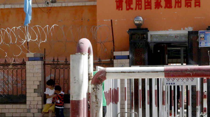 أطفال أمام أحد المراكز التي تدخل فيها الحكومة الصينية أطفال من أقلية الأيغور