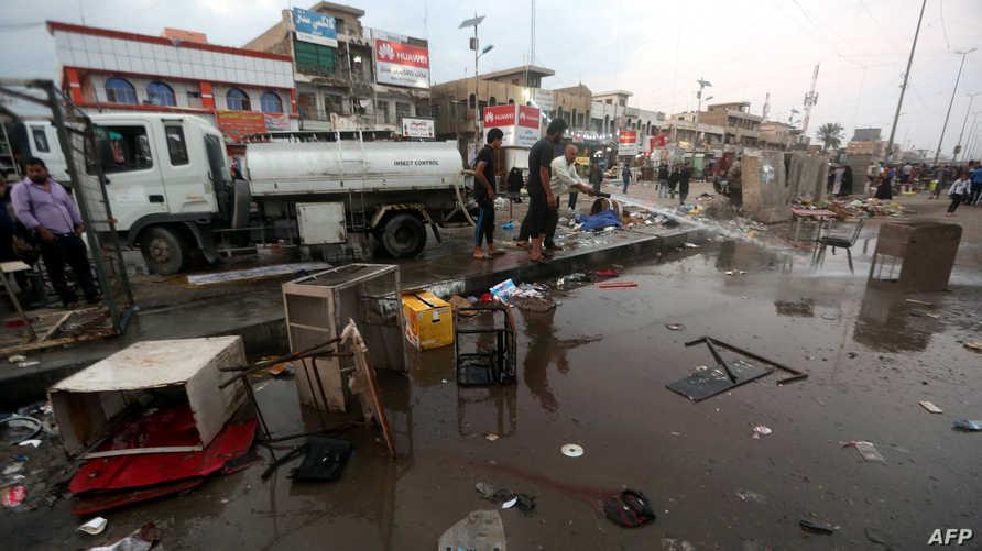 عراقيون ينظفون موقع أحد التفجيرين في مدينة الصدر في بغداد