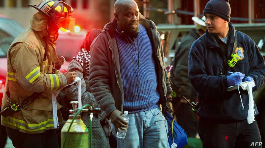 مسعفون وطواقم إنقاذ يساعدون شخصا على مغادرة محطة لنفانت بلازا في واشنطن العاصمة بعد تسرب دخان