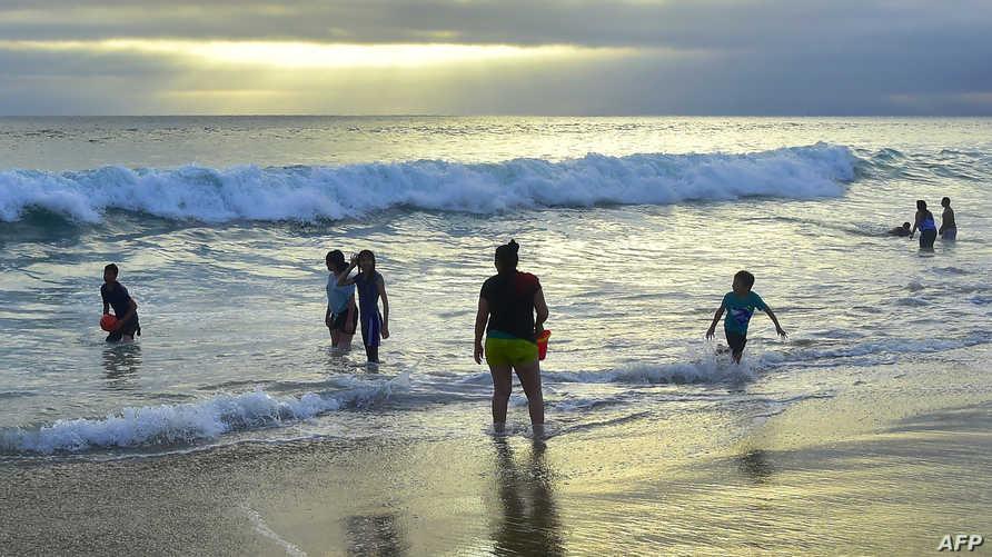 أشخاص يفرون إلى البحر هربا من الحرارة