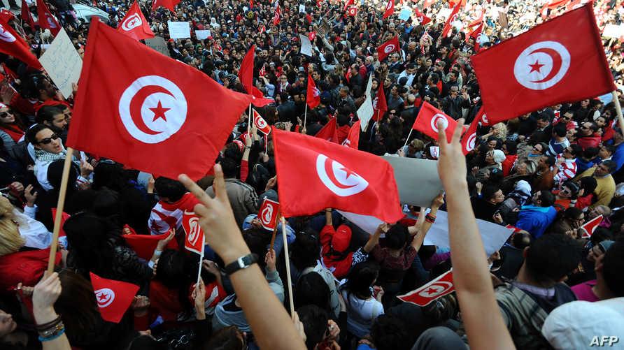 تونسيون يرفعون أعلام بلادهم خلال إحدى المظاهرات- أرشيف