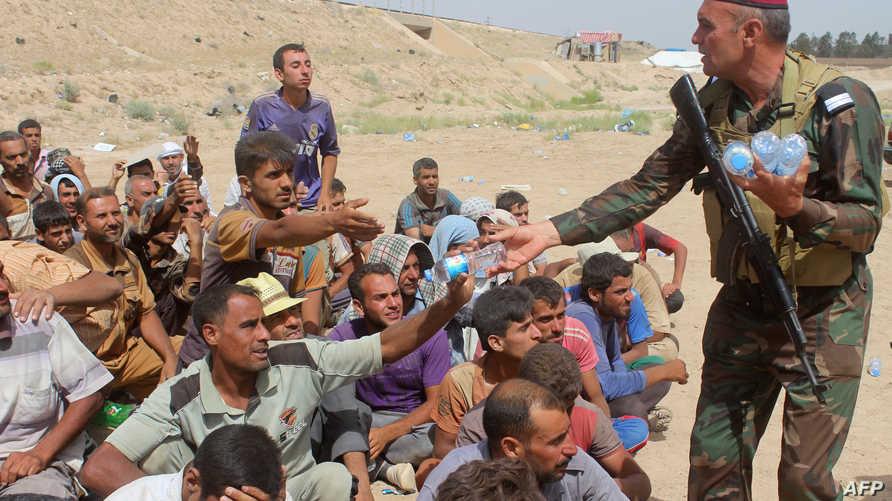جندي عراقي يوزع الماء على نازحين من أهالي قرى في الفلوجة- أرشيف