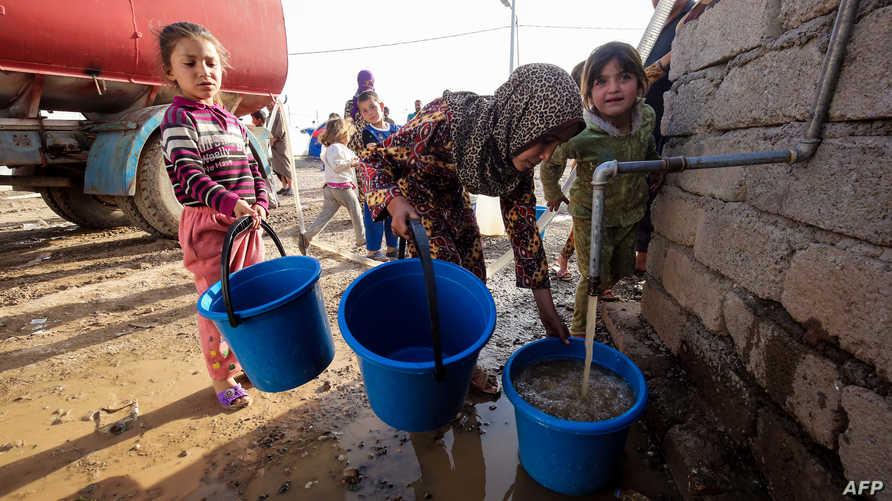 أطفال عراقيون في مخيم جنوب الموصل.