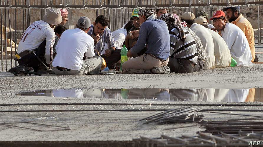 عمال أجانب يتناولون إفطارهم في ورشة بناء في العاصمة السعودية الرياض