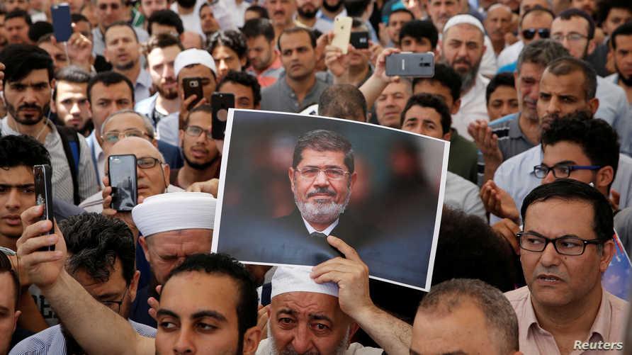 يرفع صورة مرسي بعد إقامة صلاة الغائب له في تركيا
