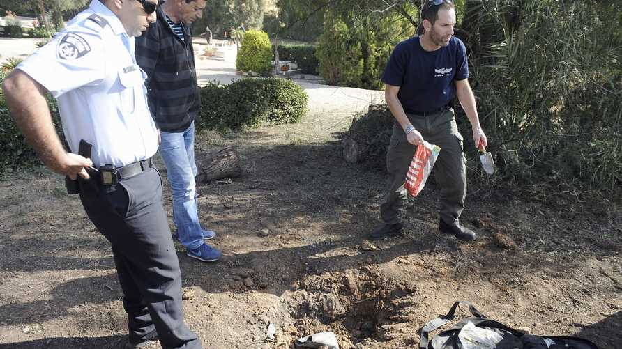 خبراء متفجرات يتفحصون آثار صاروخ أطلق من غزة على إسرائيل