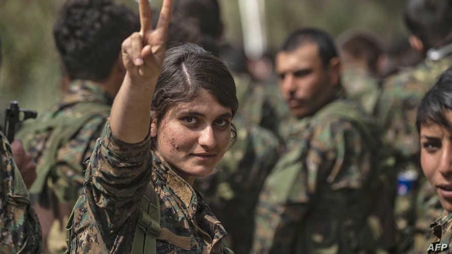 مقاتلة من قسد ترفع شارة النصر بعد إعلان دحر داعش