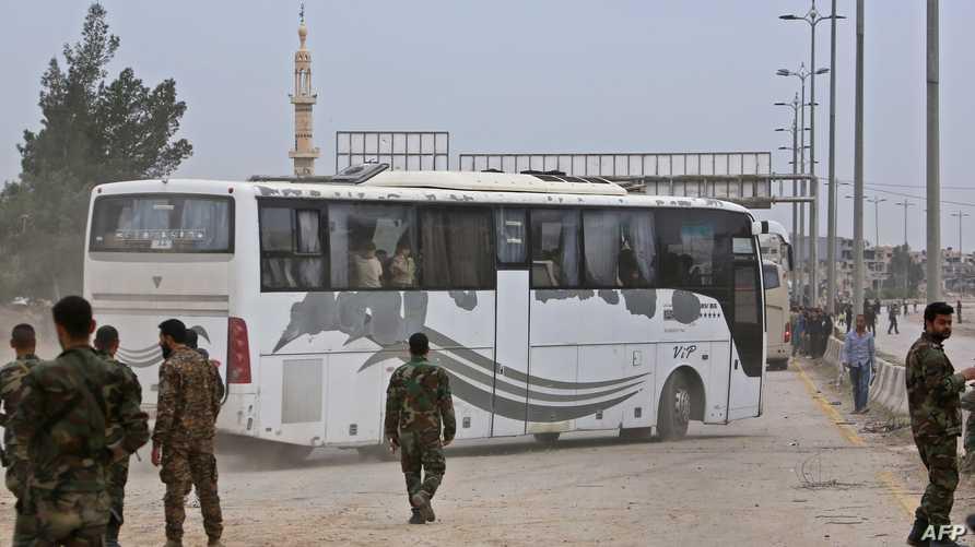جنود تابعون للنظام السوري في حراسة حافلات تضم أفرادا خرجوا من الغوطة