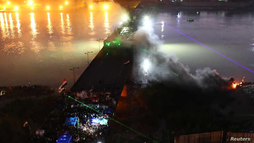 الدخان يتصاعد خلال اشتباكات بين متظاهرين وقوى الأمن العراقية على جسر الجمهورية في بغداد بتاريخ 5 نوفمبر 2019