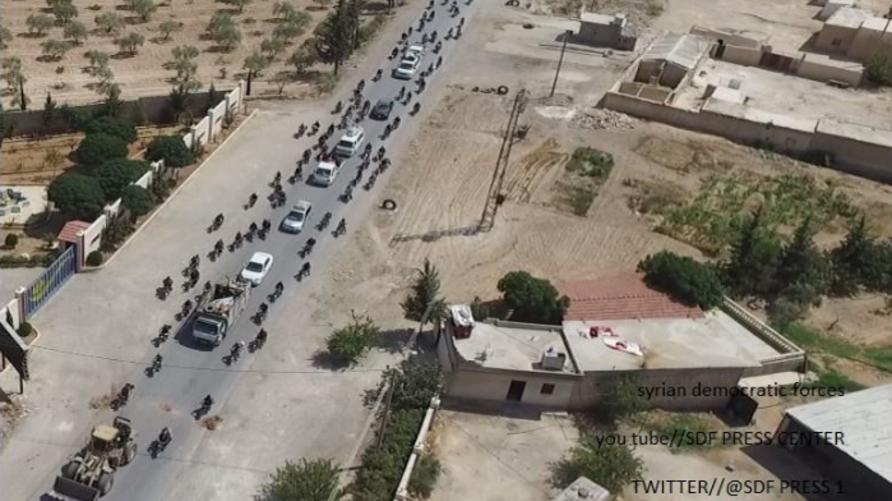 رتل سيارات لداعش محاطة بمدنيين في منبج، (موقع تويتر لقوات سورية الديموقراطية)