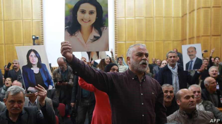 متظاهر يحمل صورة لفيغين يوكسيكداغ في البرلمان التركي