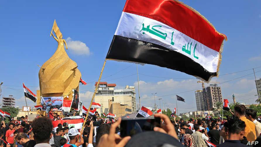 محتجون يرفعون أعلاما عراقية خلال تظاهرة وسط كربلاء