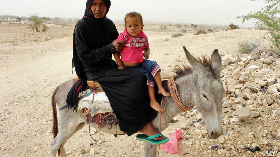 أم يمنية نازحة من مدينة الحديدة تصطحب طفلها إلى عيادة صحية في محافظة حجة