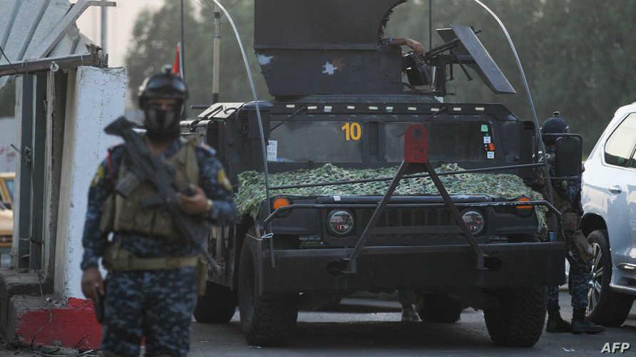 شرطي عراقي ملثم أمام سيارة تابعة للشرطة ببغداد - 7 أكتوبر 2019