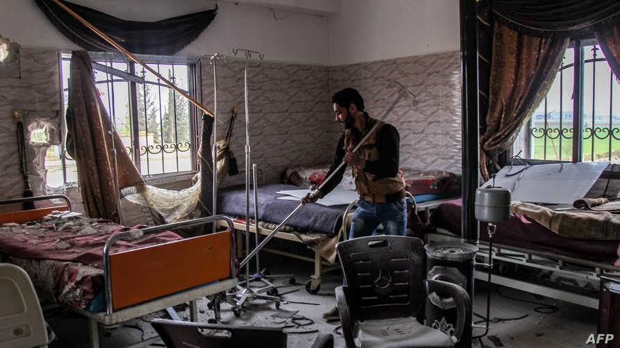 ينظف غرفة في مستشفى في بلدة سراقب في إدلب، بعد تعرضها لغاراة من طائرات النظام السوري