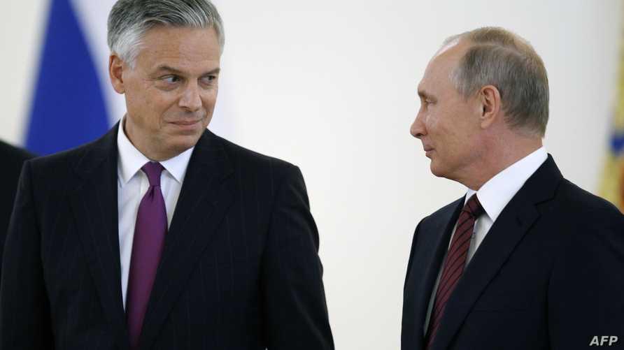 السفير الأميركي لدى موسكو جون هانتسمان (يسار) والرئيس الروسي فلاديمير بوتين