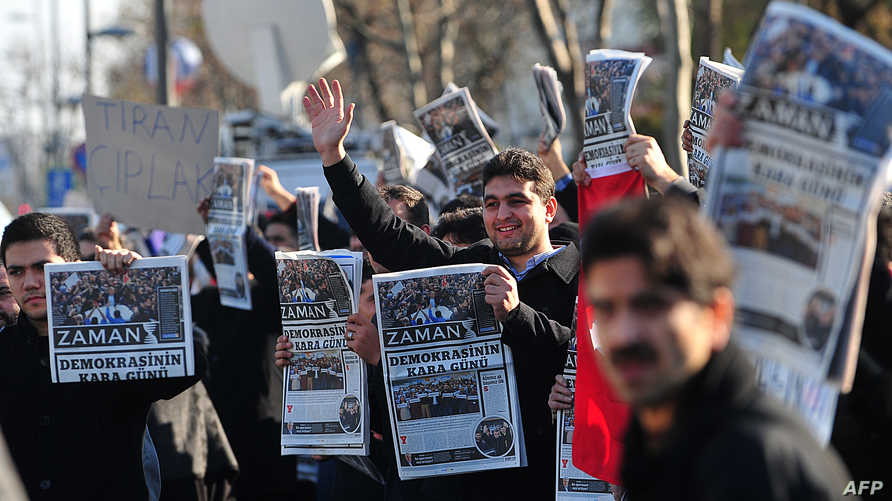 متظاهرون يرفعون نسخا من زمان للاحتجاج على توقيف صحافيين عاملين فيها-أرشيف