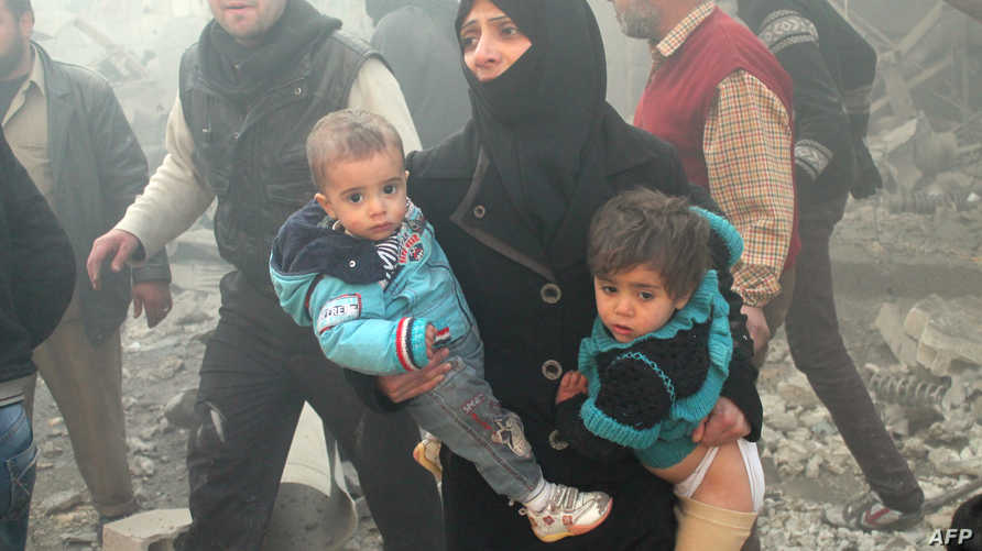 سورية تنجو بطفليها بعد تعرض حيها للقصف في حلب