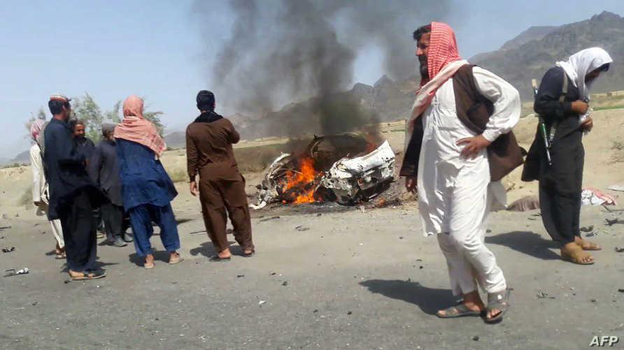 باكستانيون عند سيارة الملا منصور إثر استهدافها