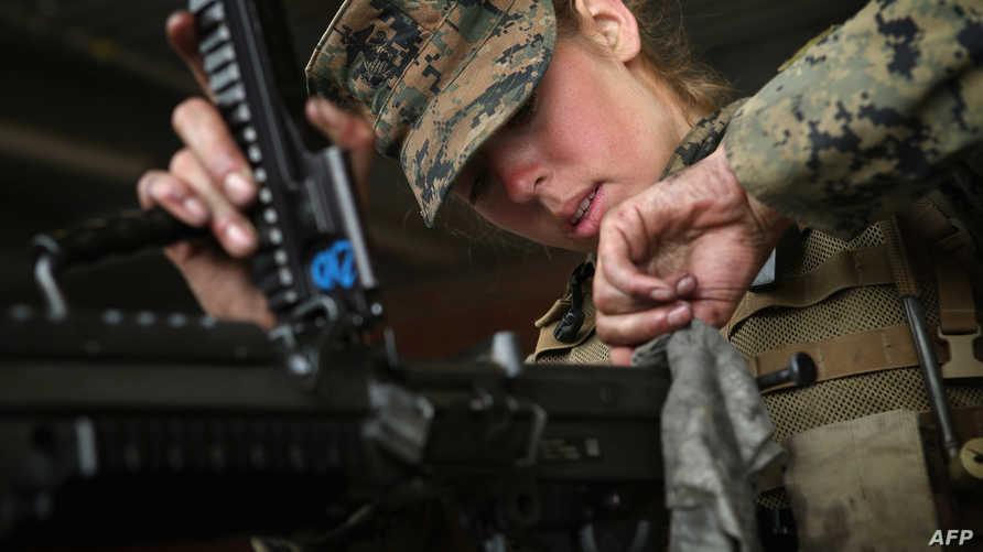 مجندة أميركية تتفقد سلاحها