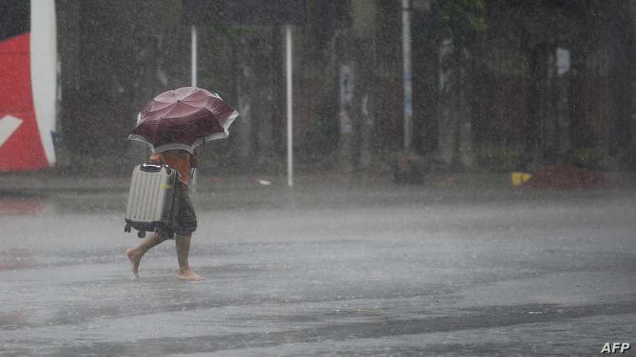 امرأة تحاول العبور وسط الأمطار الكثيفة التي صاحبت إعصار بلبل - 9 نوفمبر 2019