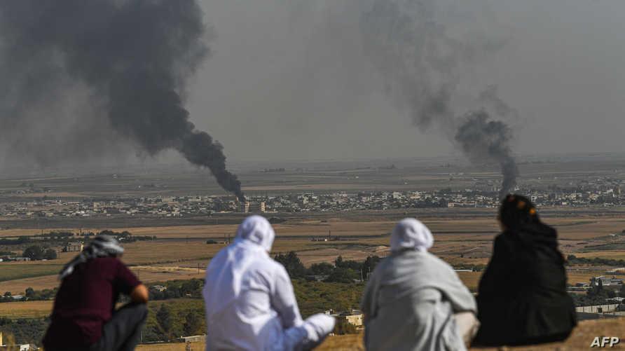 سكان ينظرون إلى الدخان المتصاعد من مدينة رأس العين الحدودية