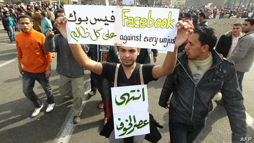 مصري يحمل لوحة مؤيدة للفيسبوك