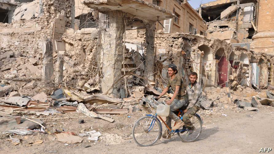 رجلان على دراجة في مدينة دير الزور