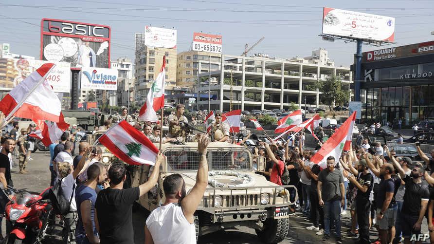 سيارة تابعة للجيش اللبناني خلال عبورها وسط المتظاهرين الذين يقومون بتحيتها بالأعلام