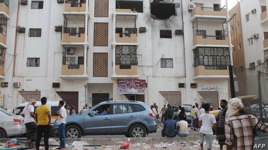 يمنيون يتفحصون موقع تفجير بعد قصف لقوات التحالف العربي
