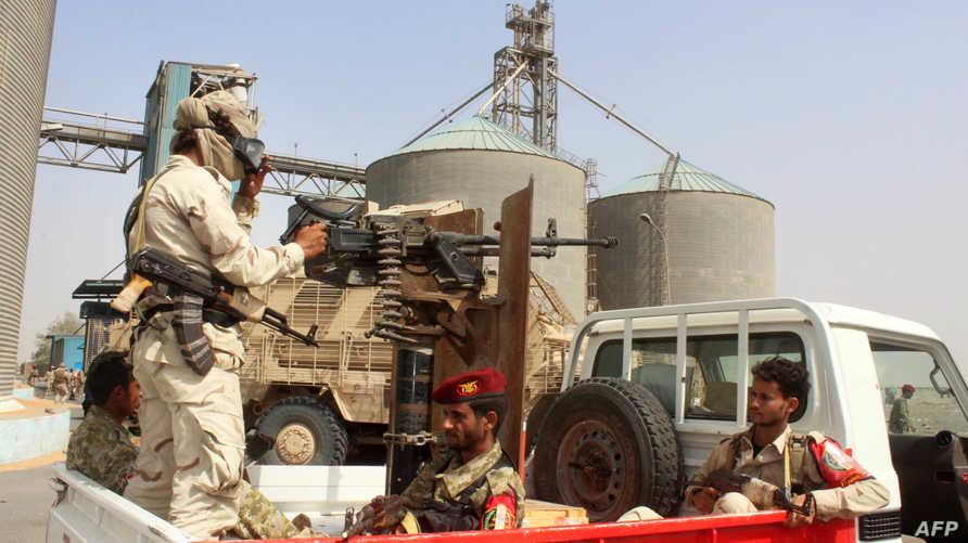 جنود يمنيون مدعمون من السعودية والإمارات، يحرسون شركة مطاحن في مرفأ الحديدة