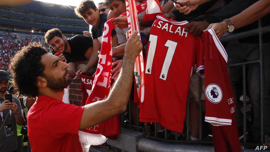 نجم ليفربول محمد صلاح يوقع على قمصان تحمل اسمه