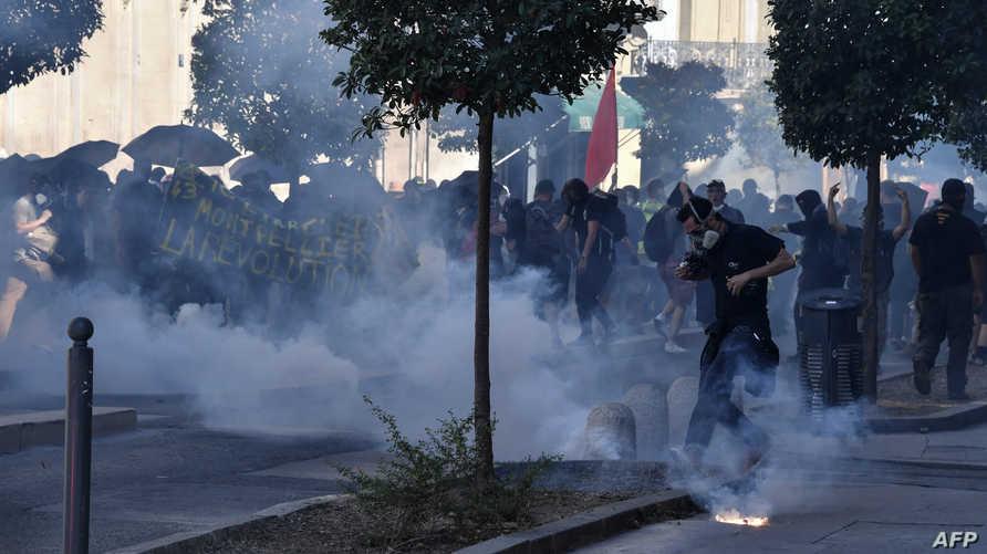 متظاهرون في هونغ كونغ يقفون وسط الدخان المتصاعد من قنابل الغاز المسيل للدموع، السبت