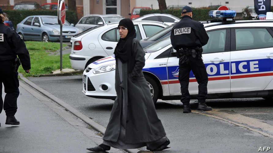 مرور فرنسية ترتدي الحجاب بالقرب من سيارة للشرطة في باريس
