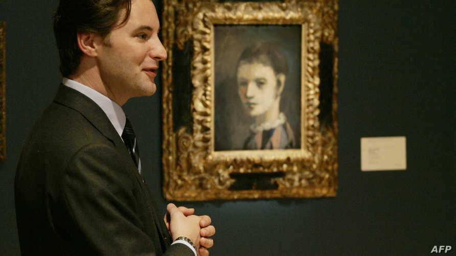 """رجل يقف أمام لوحة """"رأس أرليكينيو"""" في متحف كونستال"""