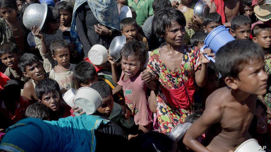 أطفال لاجئون من أقلية الروهينغا التي فر مئات الآلاف من أفرادها من ميانمار إلى بنغلادش، خلال توزيع مساعدات غذائية عليهم