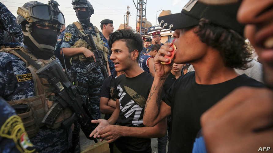 محتجون عراقيون بالقرب من عناصر أمنية في بغداد